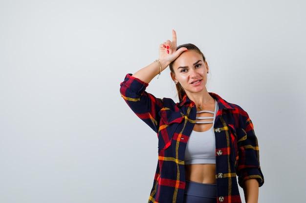 Młoda kobieta pokazuje gest przegrany w crop top, kraciaste koszule i wygląda poważnie. przedni widok.
