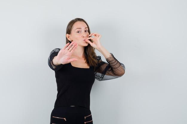 Młoda kobieta pokazuje gest pyszne i zatrzymania w czarnej bluzce i czarnych spodniach i patrząc szczęśliwy, widok z przodu.