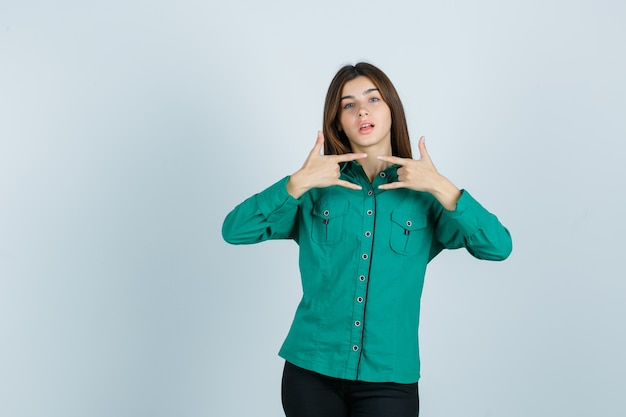 Młoda kobieta pokazuje gest rocka w zielonej koszuli i wygląda pewnie, widok z przodu.