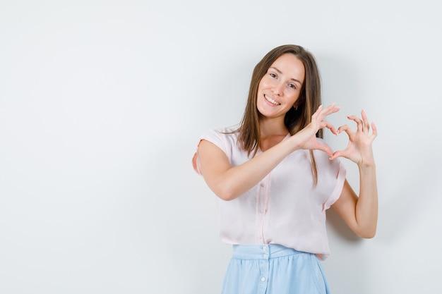 Młoda kobieta pokazuje gest serca i uśmiecha się w t-shirt, widok z przodu spódnicy.