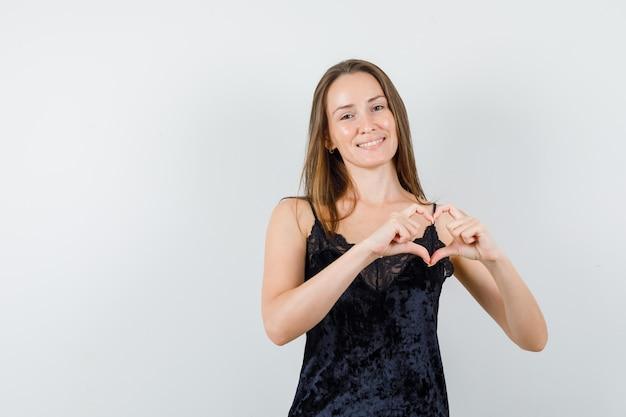 Młoda kobieta pokazuje gest serca w czarnym podkoszulku i wygląda radośnie