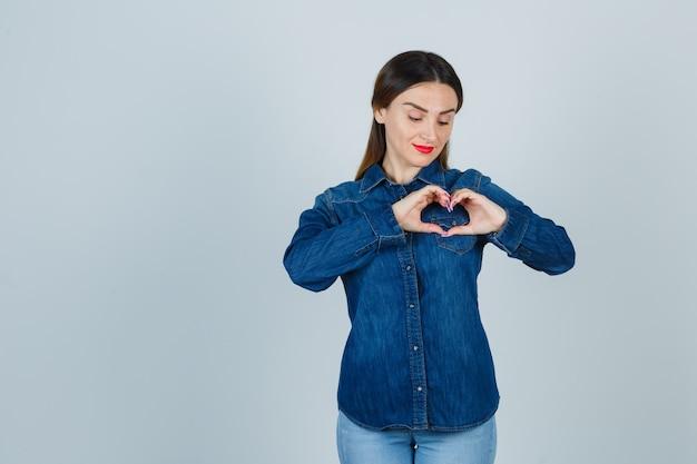 Młoda kobieta pokazuje gest serca w dżinsowej koszuli i dżinsach i wygląda ładnie