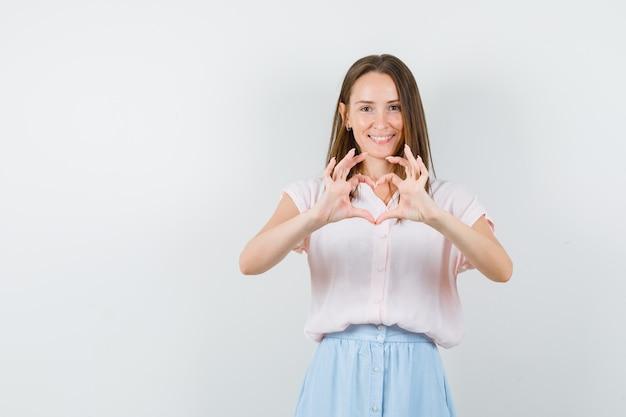 Młoda kobieta pokazuje gest serca w koszulce, spódnicy i wesoło, widok z przodu.