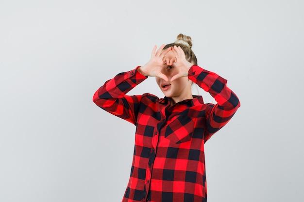 Młoda kobieta pokazuje gest serca w kraciastej koszuli i wygląda pewnie, widok z przodu.