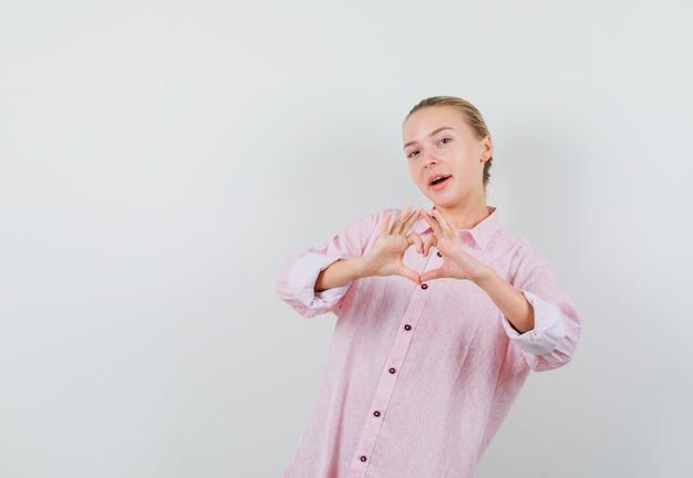 Młoda kobieta pokazuje gest serca w różowej koszuli i wygląda optymistycznie