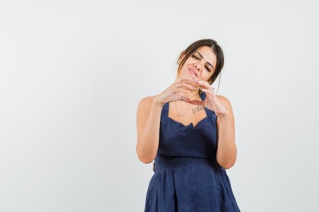 Młoda kobieta pokazuje gest serca w sukni i patrzy wesoło
