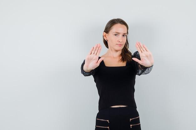 Młoda kobieta pokazuje gest stop w czarnej bluzce i wygląda poważnie