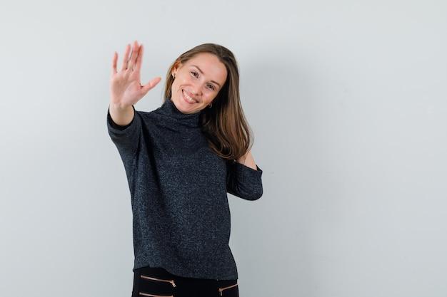 Młoda kobieta pokazuje gest stop w koszuli i szuka szczęśliwy. przedni widok.