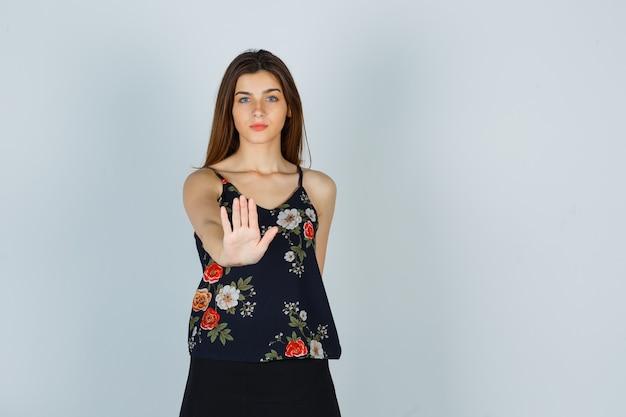 Młoda kobieta pokazuje gest stop w kwiatowy top i wygląda pewnie