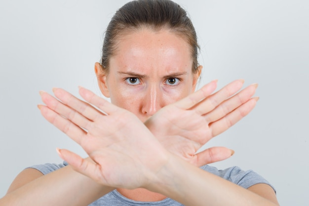 Młoda kobieta pokazuje gest stop w szarej koszulce i wygląda poważnie. przedni widok.