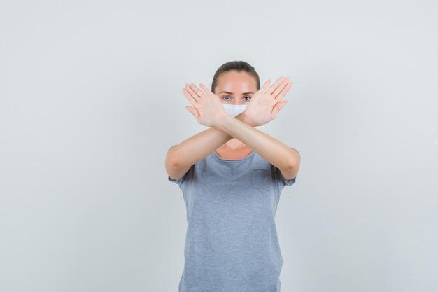 Młoda kobieta pokazuje gest stopu w koszulce, masce i szuka wyczerpany. przedni widok.