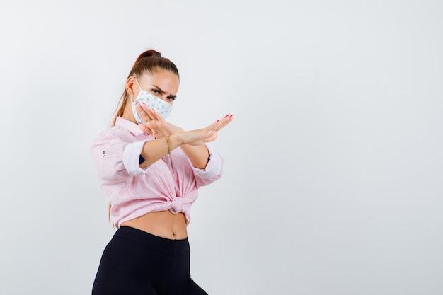 Młoda kobieta pokazuje gest stopu w koszuli, spodniach, masce medycznej i wygląda poważnie, widok z przodu.