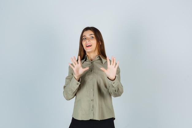 Młoda kobieta pokazuje gest stopu w koszuli, spódnicy i przestraszony
