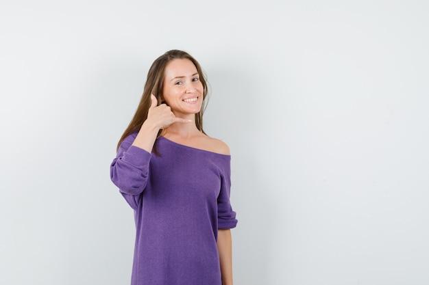 Młoda kobieta pokazuje gest telefonu w fioletowej koszuli i szuka pomocny. przedni widok.