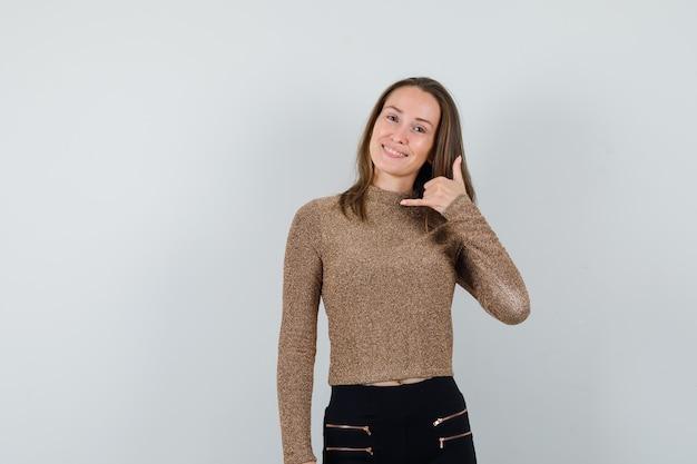 Młoda kobieta pokazuje gest telefonu w pozłacanym swetrze i czarnych spodniach i wygląda szczęśliwy