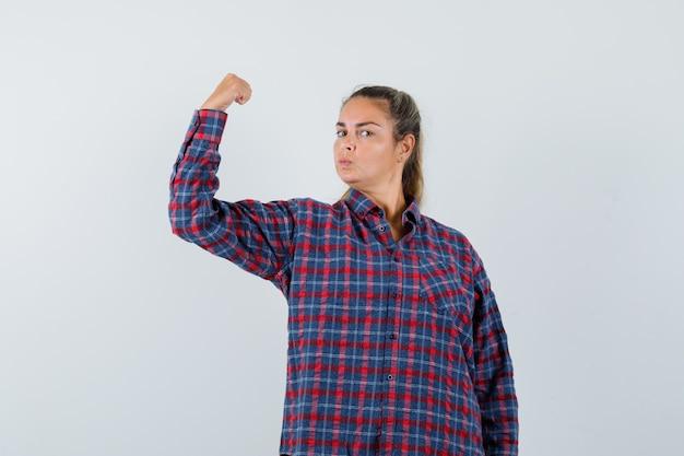 Młoda kobieta pokazuje gest władzy w kraciastej koszuli i wygląda potężnie