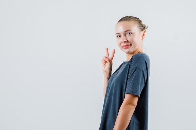 Młoda kobieta pokazuje gest zwycięstwa w szarej koszulce i wygląda wesoło.