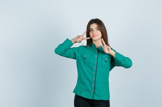 Młoda kobieta pokazuje gest zwycięstwa w zielonej koszuli i patrzy wesoło, widok z przodu.