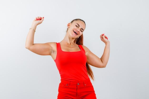 Młoda kobieta pokazuje gest zwycięzcy w czerwony podkoszulek, spodnie i wesoły, widok z przodu.