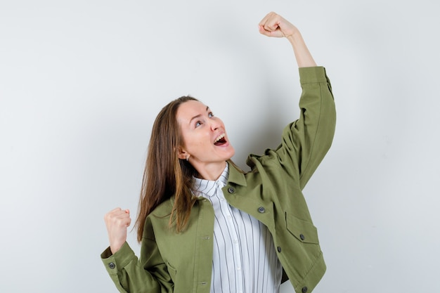 Młoda kobieta pokazuje gest zwycięzcy w koszulę, kurtkę i patrząc na szczęście, widok z przodu.