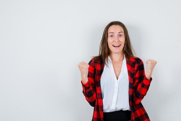 Młoda kobieta pokazuje gest zwycięzcy w ubranie i wygląda na szczęśliwego. przedni widok.