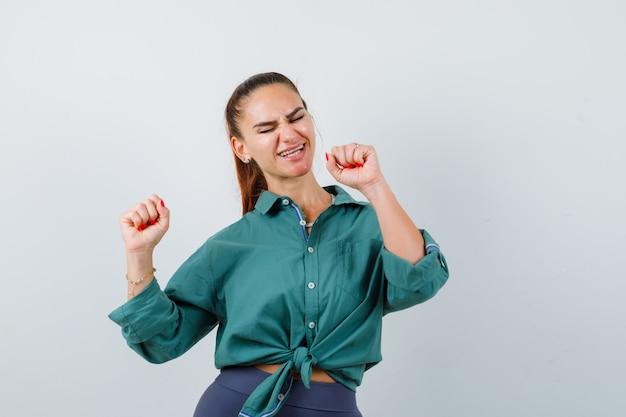 Młoda kobieta pokazuje gest zwycięzcy w zielonej koszuli i patrząc błogo. przedni widok.