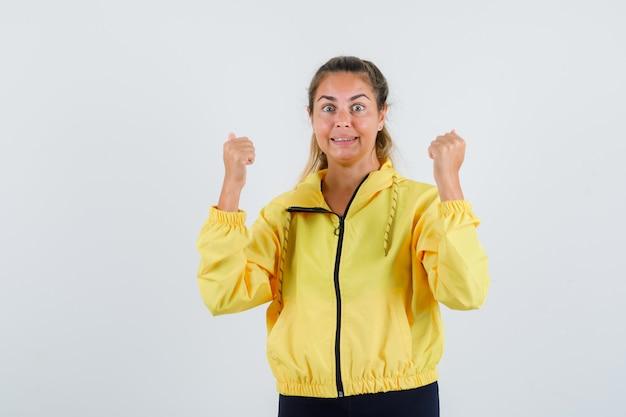 Młoda kobieta pokazuje gest zwycięzcy w żółtym płaszczu przeciwdeszczowym i szuka energiczny
