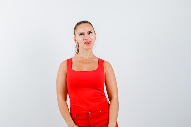 Młoda kobieta pokazuje grymas w czerwonym podkoszulku bez rękawów, spodniach i wygląda zabawnie, widok z przodu.
