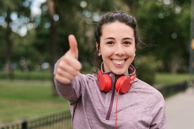 Młoda kobieta pokazuje jej aprobaty po treningu