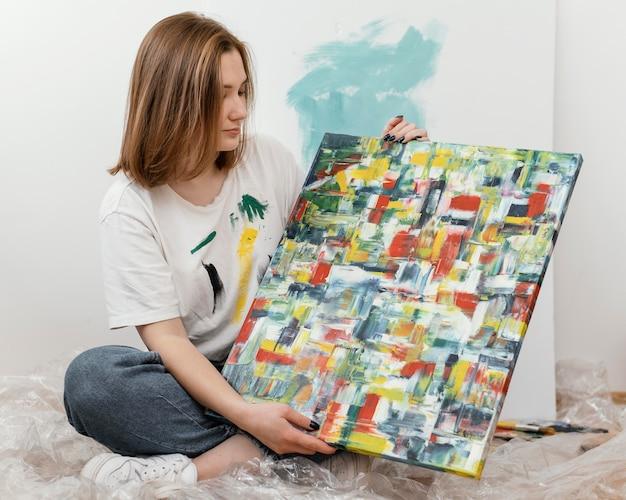 Młoda kobieta pokazuje jej obraz