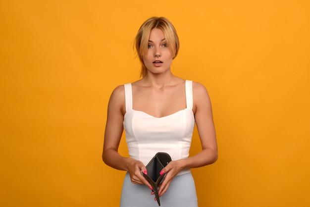 Młoda kobieta pokazuje jej pusty portfel. bankructwo