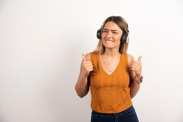 Młoda kobieta pokazuje kciuk i noszenie słuchawek na białym tle.