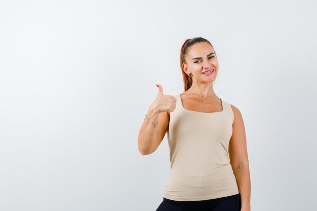 Młoda kobieta pokazuje kciuk w beżowym podkoszulku bez rękawów i wygląda zadowolony, widok z przodu.