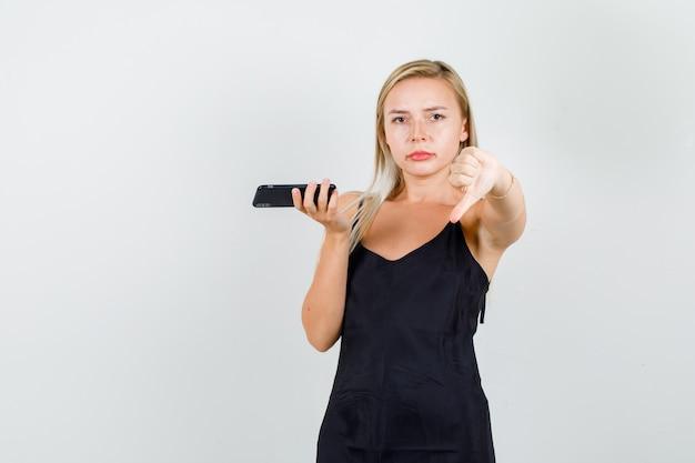 Młoda kobieta pokazuje kciuk w dół, trzymając smartfon w czarnym podkoszulku i wygląda na niezadowoloną