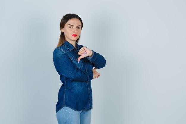 Młoda kobieta pokazuje kciuk w dół w dżinsowej koszuli i dżinsach i wygląda na niezadowolonego
