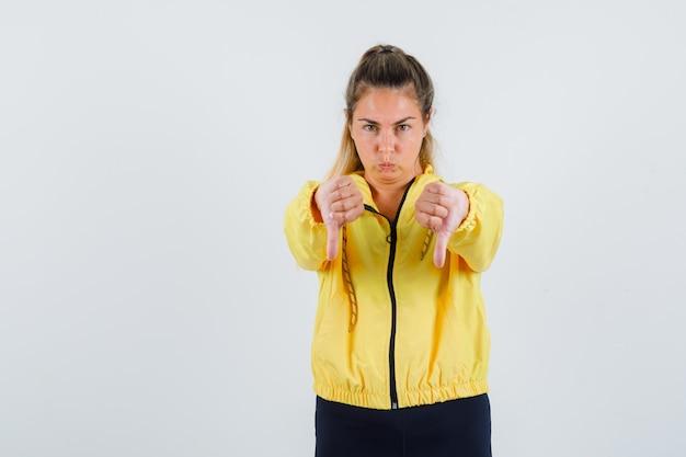 Młoda kobieta pokazuje kciuk w dół w żółtym płaszczu przeciwdeszczowym i wygląda na niezadowolonego
