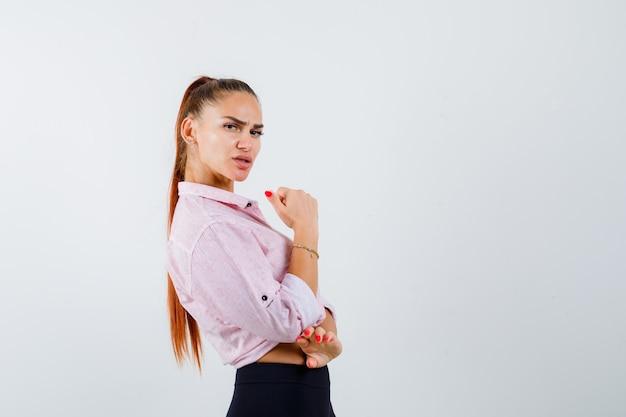 Młoda kobieta pokazuje kciuk w dorywczo koszula, spodnie i wygląda pewnie. przedni widok.