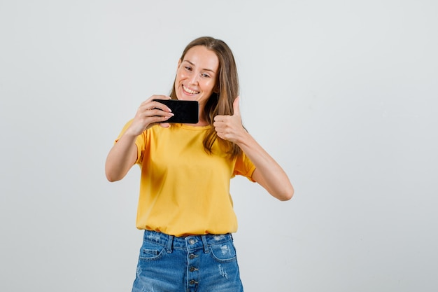 Młoda kobieta pokazuje kciuk w górę podczas robienia selfie w koszulce, spodenkach i patrząc zadowolony. przedni widok.