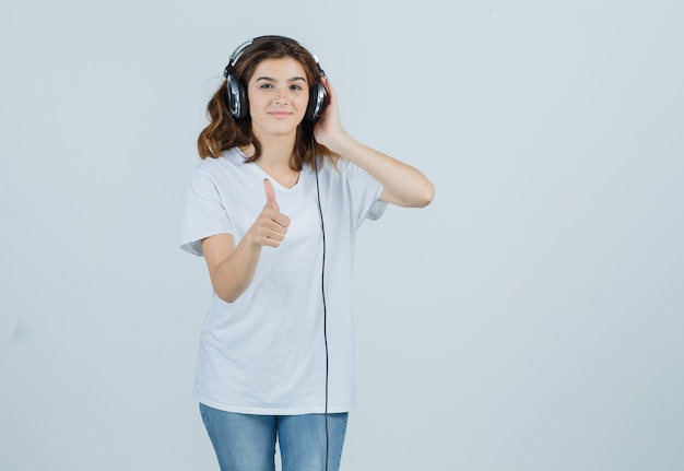 Młoda kobieta pokazuje kciuk w górę podczas słuchania muzyki w słuchawkach w białej koszulce, dżinsach i wygląda na szczęśliwego. przedni widok.