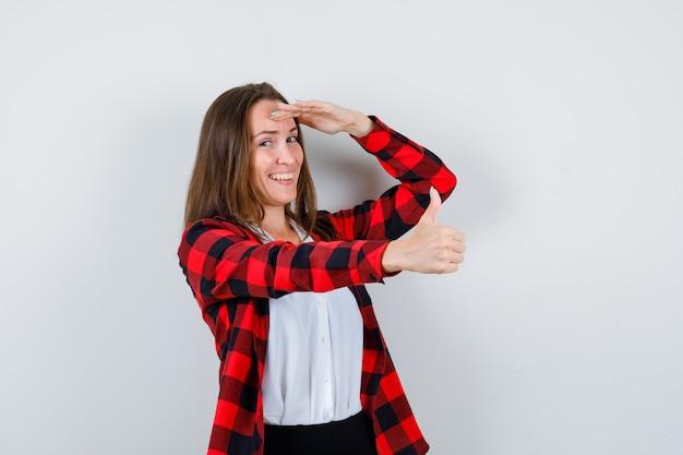 Młoda kobieta pokazuje kciuk w górę, z ręką nad głową w ubranie i patrząc wesoło, widok z przodu.