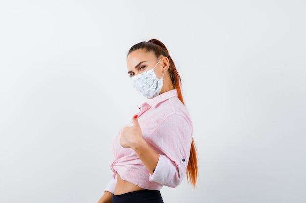 Młoda kobieta pokazuje kciuk w koszuli, spodniach, masce medycznej i wygląda zadowolony, widok z przodu.