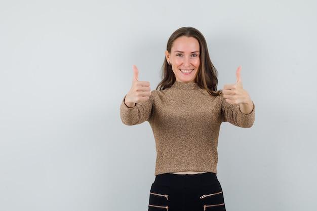 Młoda kobieta pokazuje kciuk w złotej bluzce i szuka zadowolony