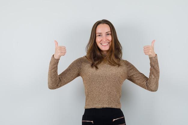 Młoda kobieta pokazuje kciuk w złotej bluzce i wygląda optymistycznie