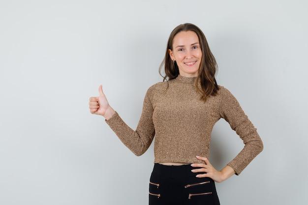 Młoda kobieta pokazuje kciuk w złotej bluzce i wygląda pewnie siebie. przedni widok.
