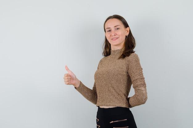 Młoda kobieta pokazuje kciuk w złotej bluzce, widok z przodu.