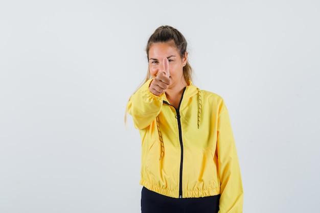 Młoda kobieta pokazuje kciuk w żółtym płaszczu i szuka zadowolony