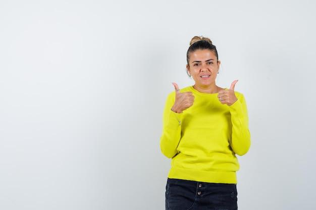 Młoda kobieta pokazuje kciuki do góry obiema rękami w żółtym swetrze i czarnych spodniach i wygląda na szczęśliwą