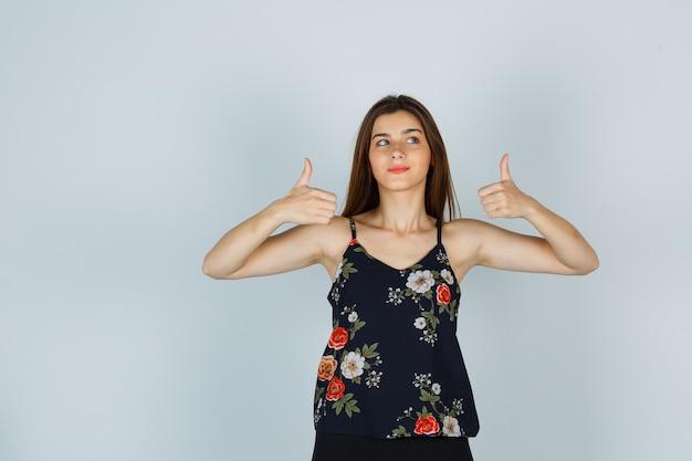 Młoda kobieta pokazuje kciuki do góry, patrząc z boku w kwiatowy top i wyglądająca uroczo