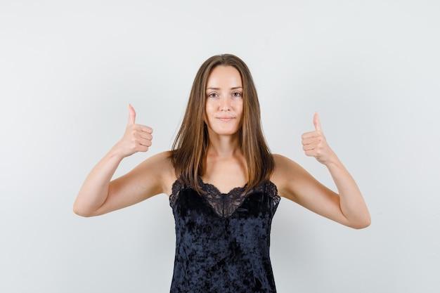 Młoda kobieta pokazuje kciuki do góry w czarnym podkoszulku i wygląda na zadowoloną