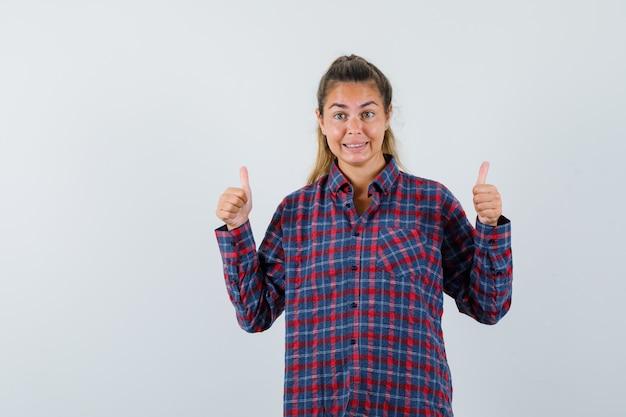 Młoda kobieta pokazuje kciuki obiema rękami w kraciastej koszuli i wygląda szczęśliwy